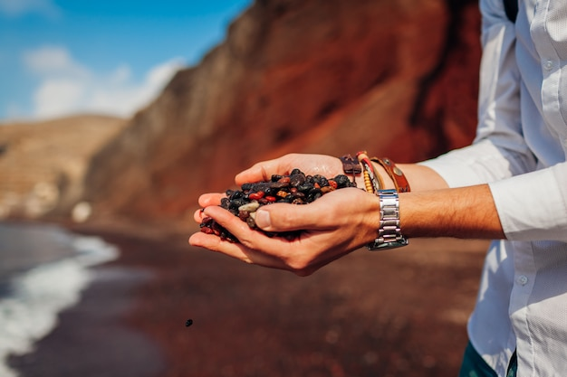 Roter strandsand. santorini-inselreisendmann, der handvoll boden, kleine steine in akrotiri, griechenland hält.