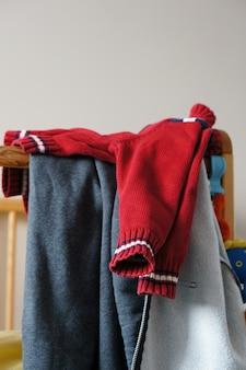 Roter strickpullover für kinder auf einem kinderbett