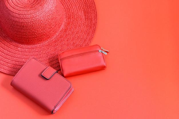 Roter strohhut und rote brieftasche auf dem roten hintergrund
