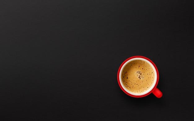 Roter tasse kaffee auf schwarzem papierhintergrund. ansicht von oben