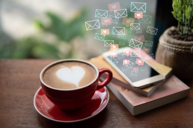 Roter tasse kaffee mit lattekunstherzform und postikone, herzikone, die vom handy fließt