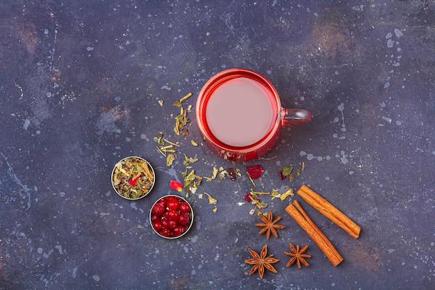 Roter tee in der glasschale und in der teekanne unter zimt, anis, preiselbeeren auf einem dunklen hintergrund. kräuter-, vitamin- und detox-tee gegen erkältung und grippe.