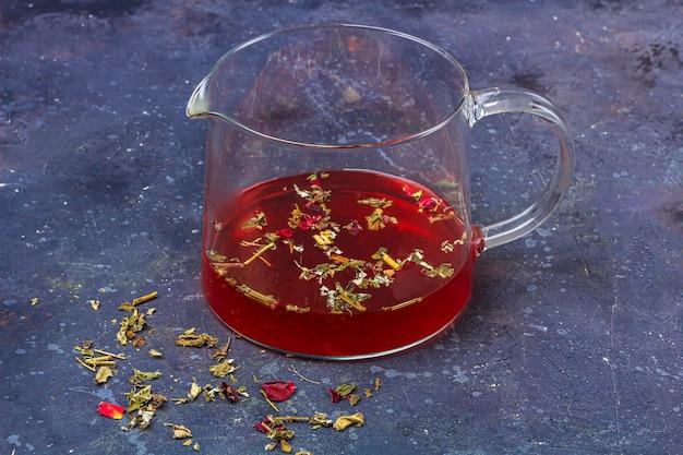 Roter tee in der glasteekanne mit trockenen teeblättern und blütenblättern auf dunklem hintergrund. kräuter-, vitamin- und detox-tee gegen erkältung und grippe.