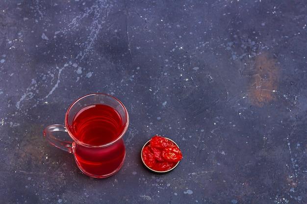 Roter tee in der türkischen teetasse mit getrockneten früchten im orientalischen stil auf dunklem hintergrund. kräuter-, vitamin- und detox-tee gegen erkältung und grippe.