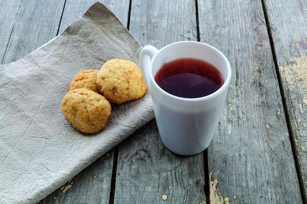Roter tee in einem weißen becher auf einem holztisch und hausgemachte kekse auf einer leinenserviette. sicht von oben