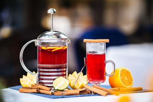 Roter tee in einer tasse und eine französische presse mit zimt