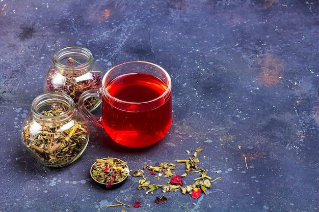 Roter tee in glasschale und gläser mit trockenem teeblatt und blütenblättern