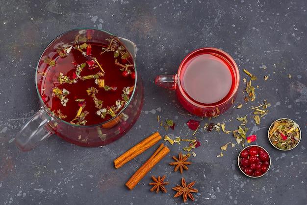 Roter tee in glasschale und teekanne zwischen trockenem teeblatt und blütenblättern