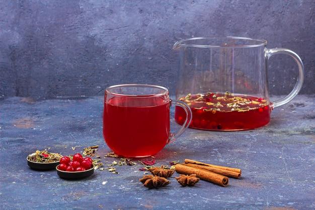 Roter tee in glasschale und teekanne zwischen zimt, anis, preiselbeeren auf einer dunkelheit