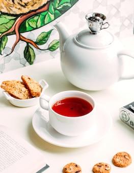 Roter tee mit ein paar keksen