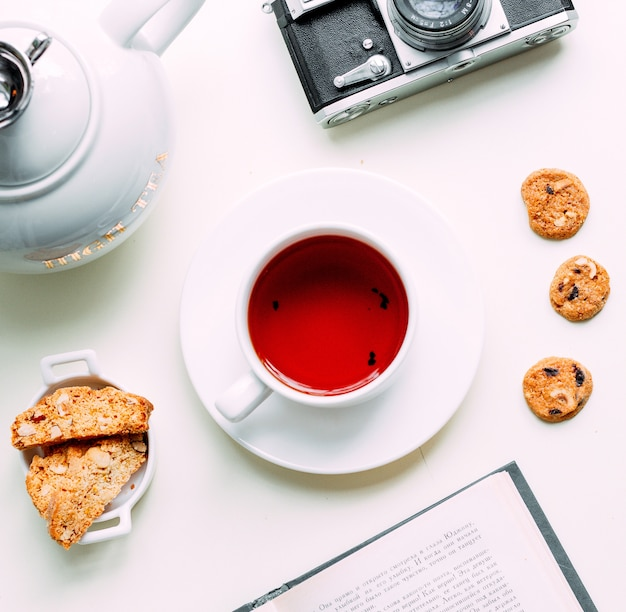Roter tee mit einigen seitlichen plätzchen