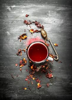 Roter tee mit granatapfel. auf einem schwarzen holztisch.