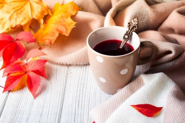Roter tee mit herbstlaub auf holzoberfläche