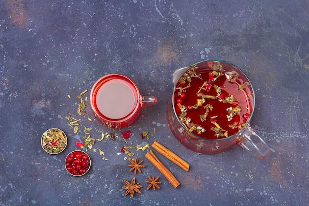 Roter tee (rooibos, hibiskus, karkade) in der glasschale und in der teekanne unter zimt, anis, preiselbeeren auf einem dunklen hintergrund. kräuter-, vitamin- und detox-tee gegen erkältung und grippe. schließen sie, kopieren sie platz für text