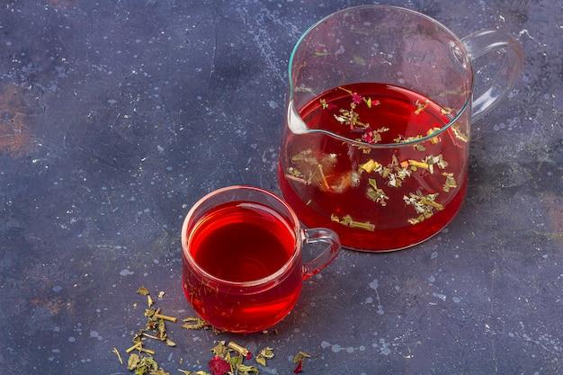 Roter tee (rooibos, hibiskus, karkade) in der glasschale und in der teekanne zwischen trockenem teeblatt und blütenblättern auf einem dunklen hintergrund. kräuter-, vitamin- und detox-tee gegen erkältung und grippe. schließen sie, kopieren sie platz für text
