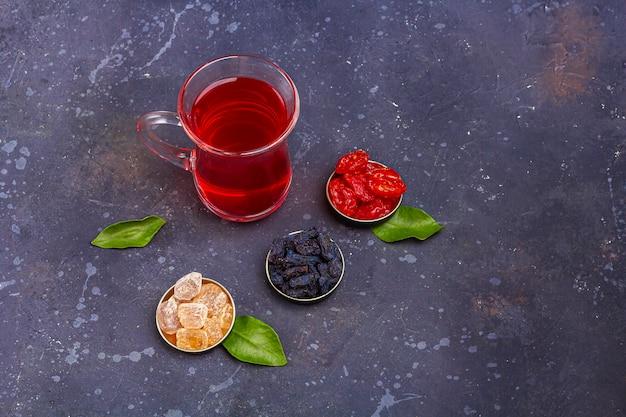 Roter tee (rooibos, hibiskus, karkade) in der türkischen teetasse (armudu) mit hartriegel, rosinen, zucker im orientalischen stil auf dunklem hintergrund. kräuter-, vitamin- und detox-tee für erkältungs- und flurtext