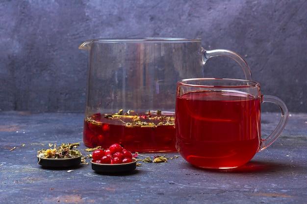 Roter tee (rooibos, hibiskus, karkade) in glasschale und teekanne zwischen trockenem teeblatt,