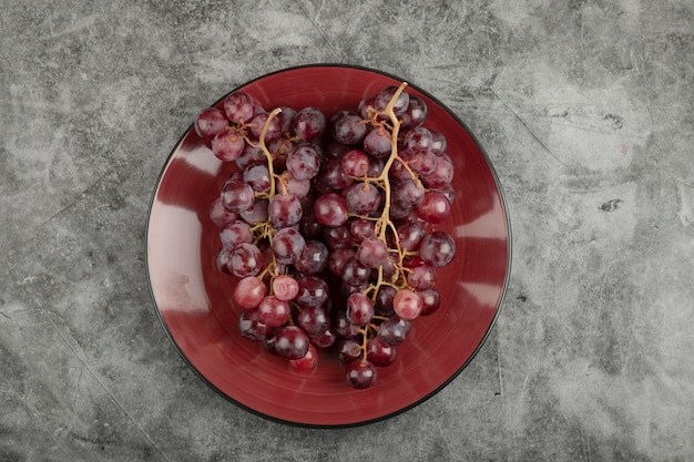 Roter teller mit frischen trauben auf marmoroberfläche.