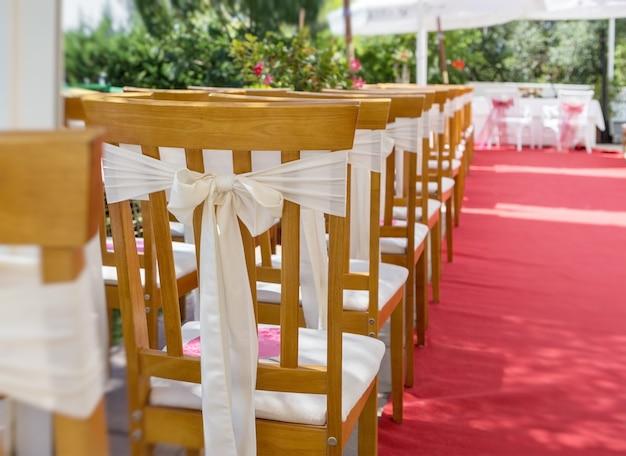 Roter teppich und dekorationen bei einer hochzeitszeremonie. stuhl nahaufnahme.