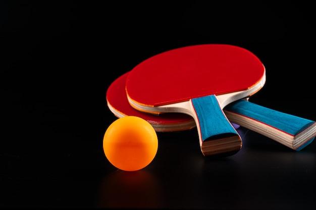 Roter tischtennisschläger auf dunkelheit. sportausrüstung