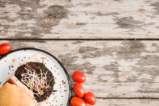 Roter tomaten- und veggiequinoaburger mit sprösslingen und leinsamen auf weißer platte über der tabelle