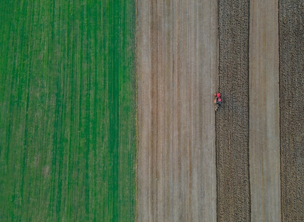 Roter traktor mit in einem feld zum pflügen der landluftansicht des landwirtschaftlichen feldes
