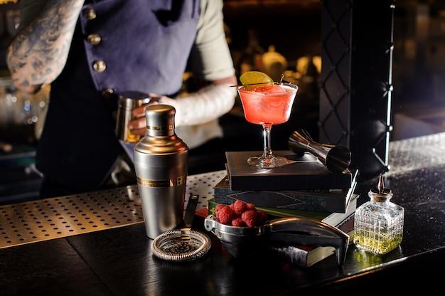 Roter transparenter cocktail, der auf den büchern steht