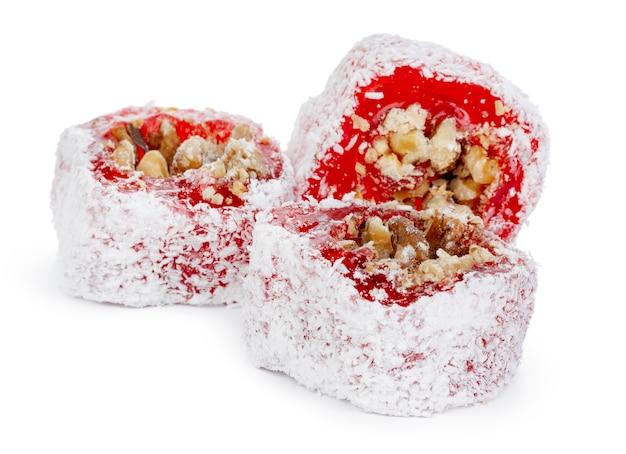 Roter türkischer genuss mit nüssen im puderzucker lokalisiert auf weiß
