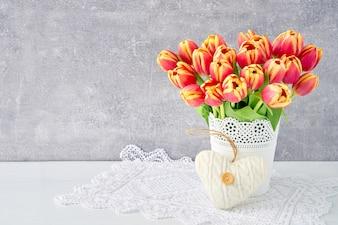 Roter Tulpenblumenstrauß im Vase verziert mit Herzen. Valentinstag, Muttertag, Geburtstagskonzept.