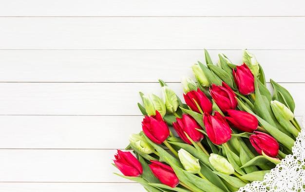 Roter tulpenblumenstrauß verziert mit spitze auf weißem holztisch.