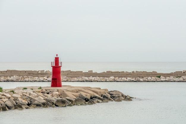 Roter turm, der um den strand unter einem klaren blauen himmel steht