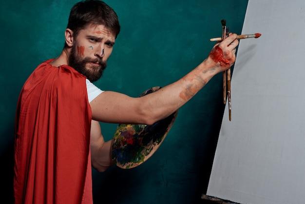 Roter umhang des männlichen künstlers, der staffelei-kunstgrün zeichnet