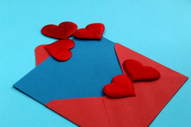 Roter umschlag mit einem blauen blatt papier und mit herzen neben, um text zu schreiben und einen brief für den feiertag happy valentinstag zu senden