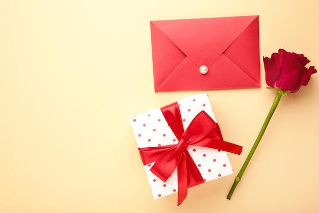 Roter umschlag mit einem brief, einem geschenk und roten rosen auf beiger oberfläche