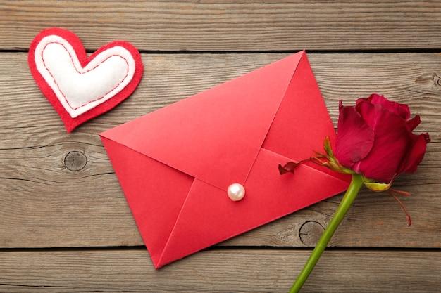 Roter umschlag mit einem brief und roten rosen auf grauer oberfläche