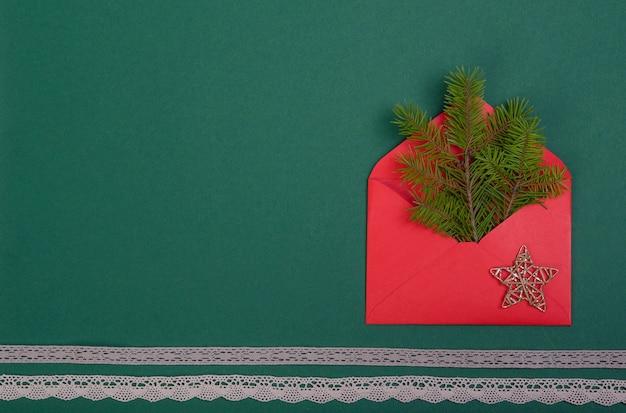 Roter umschlag mit einem neujahrsstern und spitzenbändern auf einem grünen hintergrund.