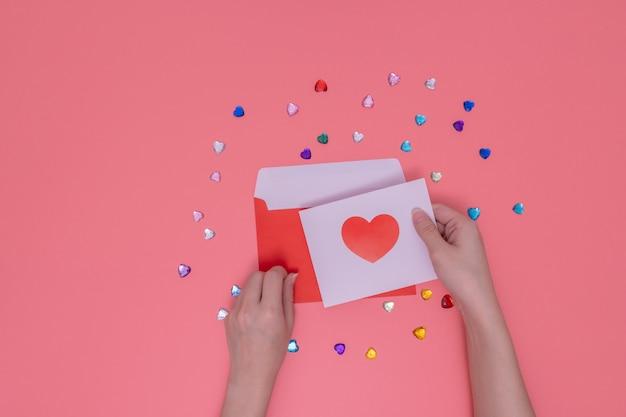 Roter umschlag und rechte hand, die ein rotes herz in einem weißen papier halten.