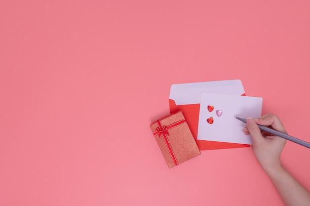 Roter umschlag und rote geschenkbox neben auf rosa