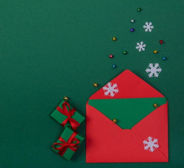 Roter umschlag und zwei weihnachtsgeschenke auf einem grünen hintergrund.
