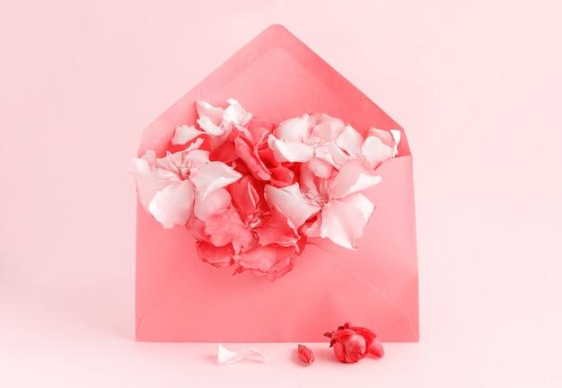 Roter umschlag voller blumen über einem rosa hintergrund schließen
