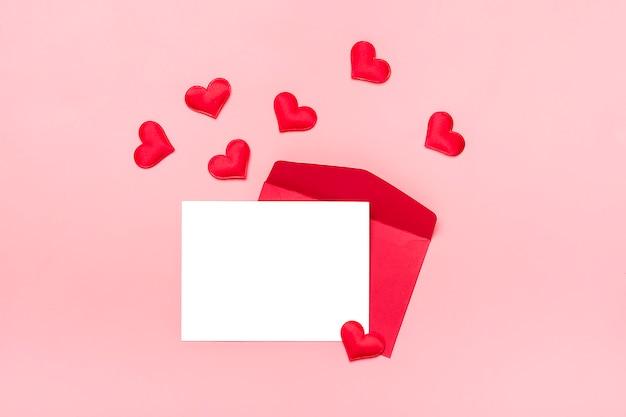Roter umschlag, weißes briefpapier, herzen auf rosa hintergrund glückliches valentinstagkonzept