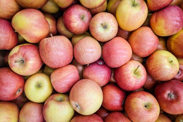 Roter und gelber apfelhintergrund. im laden angebaute frische apfelsorte. apfel geeignet für saft, strudel, apfelmus, kompott