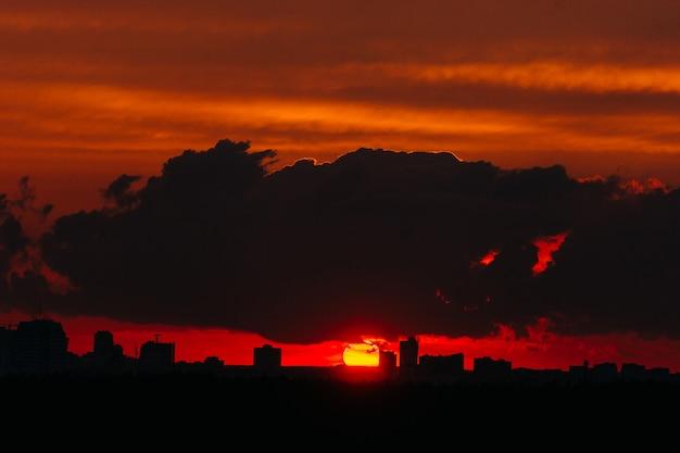 Roter und gelber sonnenuntergang über der stadt bedeckt durch wolken.