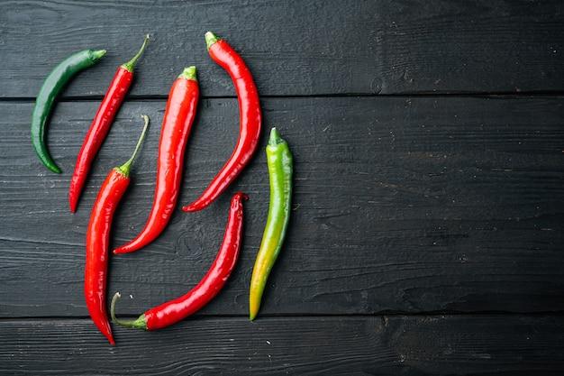 Roter und grüner chili-pfeffer-satz, auf schwarzem holztischhintergrund, draufsicht-flachlage, mit copyspace und platz für text