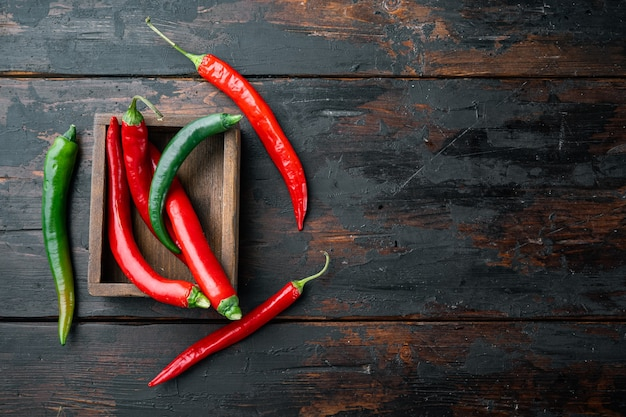 Roter und grüner chili-pfeffer-satz, in der holzkiste, auf dunklem hölzernem hintergrund, draufsicht flach, mit copyspace und raum für text