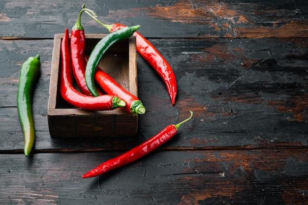 Roter und grüner chili-pfeffer-satz, in der holzkiste, auf dunklem hölzernem hintergrund, mit copyspace und raum für text