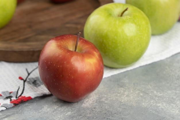Roter und grüner frischer apfel, der um holzteller gelegt wird.