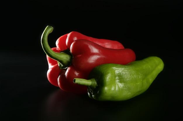 Roter und grüner pfeffer auf schwarzem