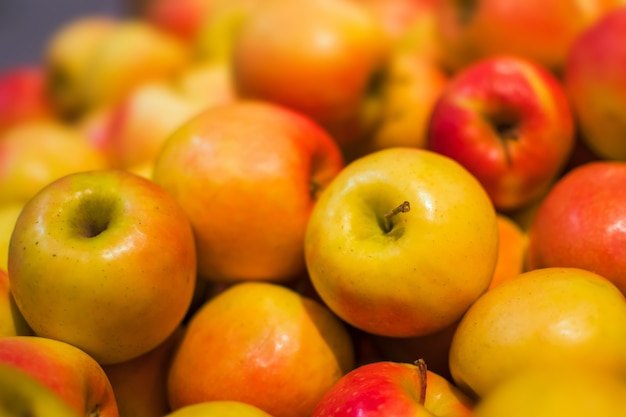 Roter und orange apfelhintergrund voll von orangen. frischer roter apfel auf dem markt.
