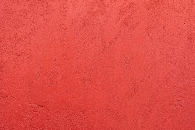 Roter und rauer wandbeschaffenheitshintergrund.